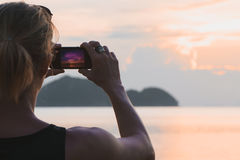 Man taking photo in picturesque sea scenery at sunset Royalty Free Stock Photography