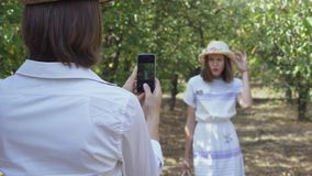 The man taking photo of pretty woman in hat. Cute couple spending time together in the park. Lovers have fun outdoors. Cute couple spending time together in the stock footage