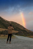 Man taking photo of rainbow over mountain Stock Images