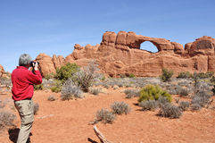 Man Taking a Photo of the Skyline Arch in Arches National Park Royalty Free Stock Image