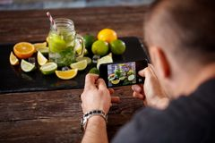 Taking photo on smartphone of mojito drink Stock Photos