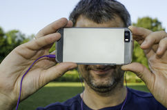 A man taking a photo with a smartphone. A man takes a photo with his smartphone and listens to music in the park on a summer afternoon stock images