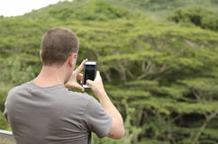 Man taking photo with smartphone. Man taking photo with smartphone of a waterfall in Kauai Royalty Free Stock Images