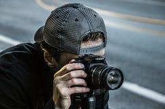 Man Taking Photo Using Black Canon DSLR Camera stock images