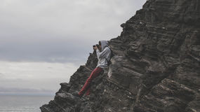 Man Taking a Photo Using Dslr Camera on Edge of Mountain Under Gray Sky Royalty Free Stock Images