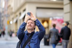 Man taking photo using his smart phone. Middle age tourist taking mobile photo using his smart phone Royalty Free Stock Images