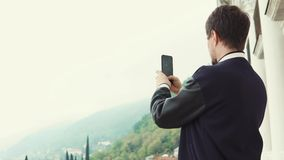 Man is taking photo and video by his phone of landscape, standing on balcony stock video footage