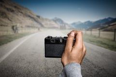 Man taking photo with vintage camera . Mixed media Royalty Free Stock Photo