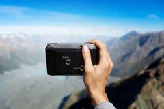 Man taking photo with vintage camera . Mixed media Royalty Free Stock Photography