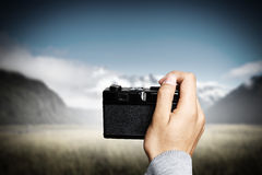 Man taking photo with vintage camera . Mixed media Stock Photos