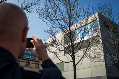 Man taking a photo wiht his smartphone. ZURICH, SWITZERLAND - MARCH  14, 2014: Man taking a photo wiht his smartphone of the Google Corporation Building Royalty Free Stock Photo