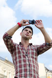 Man taking a photograph. Low angle view of a young man taking a photograph with a compact camera against a cloudy blue sky Royalty Free Stock Photos