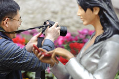 A man taking a photograph beside a girl statue Stock Photos
