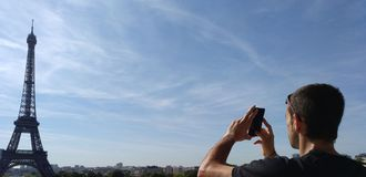 Man taking a photograph of Eiffel tower in Paris. Man taking a photograph with his mobile of Eiffel tower in Paris Stock Photography