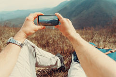 Man taking photographs mountain with smartphone Royalty Free Stock Photos