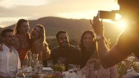 Man taking photos at dinner party. Group of young friends sitting around table and posing while a man taking their picture with her mobile phone. Man taking stock video footage