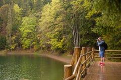 Man taking photos of  the lake on the veranda Royalty Free Stock Image