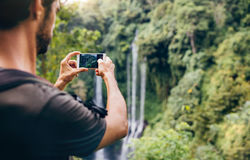 Man taking photos of waterfall with his cellphone Royalty Free Stock Photography