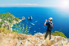 Man taking picture of beautiful landscape on mountain top. Young caucasian tourist taking picture of famous faraglioni rocks in sea with his smartphone on top of Royalty Free Stock Images