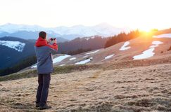 Male tourist enjoying beautiful panorama in the evening. Man taking picture of beautiful scenery in mountains during spring colorful sunset Royalty Free Stock Photography