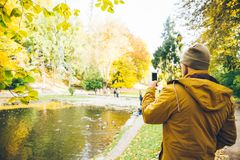 Man taking picture in city park on the lake. In autumn day Stock Photo