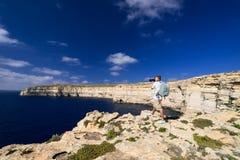 Man taking picture of coastline near Azure Window on Gozo Island Royalty Free Stock Photography