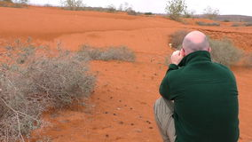 Man taking picture in desert stock video