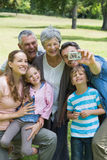Man taking picture of extended family at park Stock Image