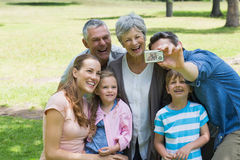 Man taking picture of extended family at park Stock Images