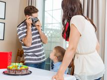 Man Taking Picture Of Family At Birthday Party Stock Image