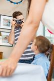 Man Taking Picture Of Family At Birthday Party Stock Photo