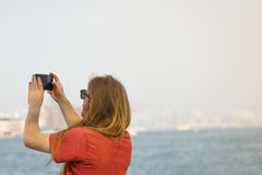 Man taking Picture on the Harbour. Man with long Hair taking Pictures in  Pier of Central Island, Hong Kong Royalty Free Stock Images