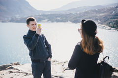 Man taking picture of his girlfriend using his smartphone near seaside and mountains Stock Images