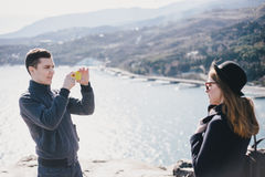 Man taking picture of his girlfriend using his smartphone near seaside and mountains Stock Photo