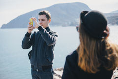 Man taking picture of his girlfriend using his smartphone near seaside and mountains Stock Photography
