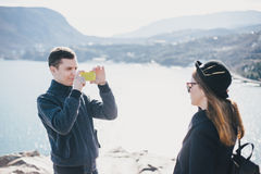 Man taking picture of his girlfriend using his smartphone near seaside and mountains Stock Image