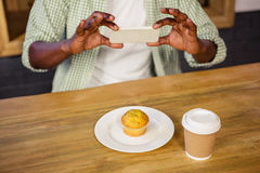 Man taking picture of a muffin Stock Photo