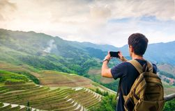Man taking picture of stunning Asian rice terrace landscape. View royalty free stock image