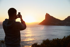 Man Taking Picture Of Sun Setting Over Sea On Mobile Phone Royalty Free Stock Photography