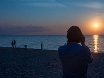Man Taking Picture at Sunset on Beach Royalty Free Stock Image