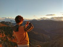 Man taking picture of sunset in mountains Royalty Free Stock Images