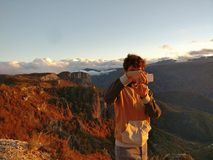 Man taking picture of sunset in mountains Stock Images