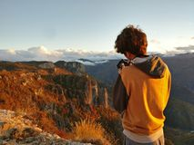Man taking picture of sunset in mountains Stock Photography