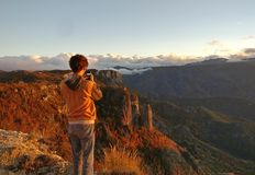 Man taking picture of sunset in mountains Stock Photo
