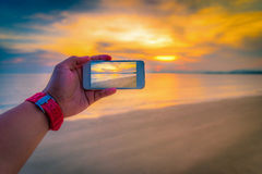 Man taking a picture of the sunset over sea Stock Photo