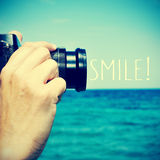 Man taking a picture and the text smile!, with a retro effect Stock Image
