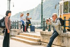 A man taking a picture of a woman with a mobile phone and another couple with suitcases. Budapest, Hungary - September 27, 2017: Close up side view of two Royalty Free Stock Image