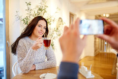 Man taking picture of woman by smartphone at cafe Royalty Free Stock Image
