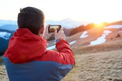 Male tourist enjoying beautiful panorama in the evening. Man taking picture of wonderful scenery in mountains during spring colorful sunset. Focus on mobile Stock Photography