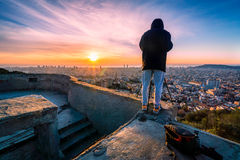 Man photographer looking and taking pictures of the city of Barcelona at sunrise. Male professional photographer standing on the edge of a fort wearing a black Stock Photos